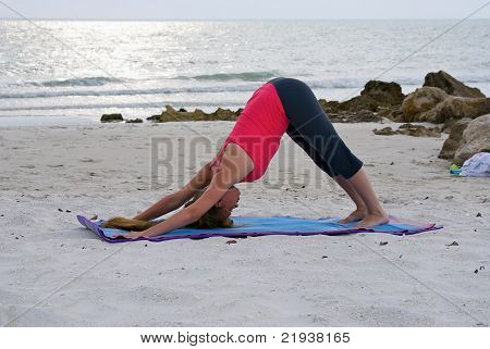 Woman Doing Yoga Exercise Downward Facing Dog Pose Or Adho Mukha Svanasana Posture On Beach At Sunse
