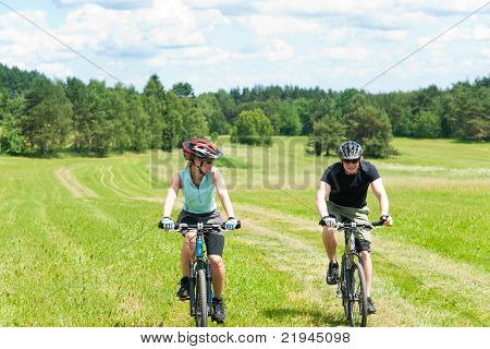Sport Happy Couple Riding Bicycles In Countryside