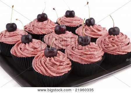 Chocolate flavored cupcakes, with red frosting and a cherry on top