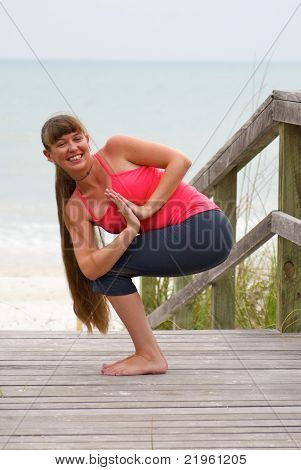 Happy Woman Doing Yoga Exercise Rotated Awkward Chair Pose On Boardwalk At Beach During Sunset