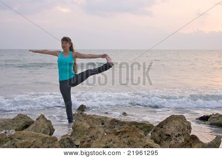 Woman Doing Yoga Exercise Extended Standing Hand To Toe Pose In Water At Ocean During Sunset