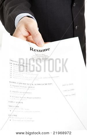 Closeup of a businessman's hand holding out a resume.  Focus on the hand and the word Resume.