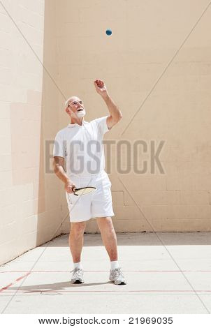 Active senior man tosses the racquetball in the air.