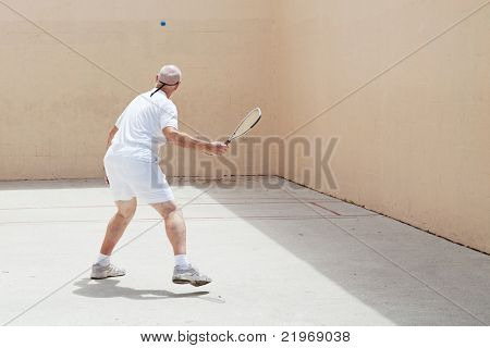 Senior man playing racquetball on an outdoor court.