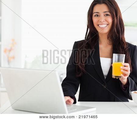 Beautiful Woman In Suit Relaxing With Her Laptop While Holding A Glass Of Orange Juice