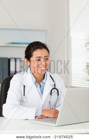 Lovely Female Doctor Working With Her Laptop While Sitting