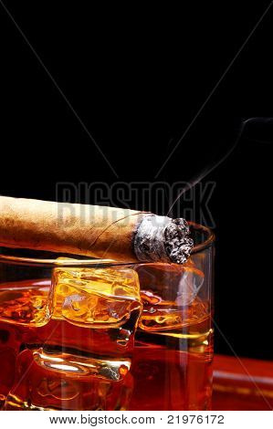 Lit Cigar resting on Glass of Whiskey and Ice cubes with wisp of smoke and black background