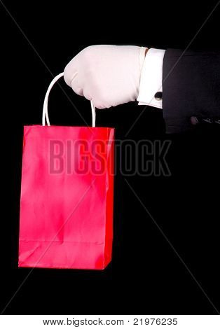 Formal Gloved Hand holding Red Gift Bag over Black Background