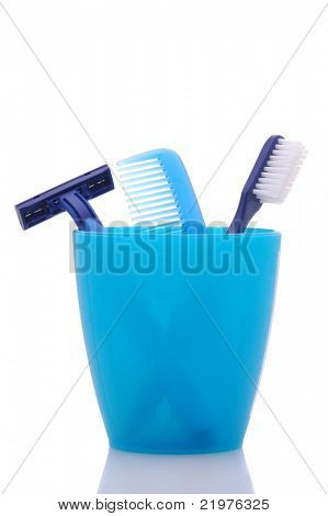 Blue Razor, Comb and Toothbrush in Cup isolated over white