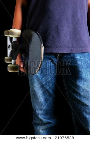 Teen Holding His Skateboard isolated over Black close up
