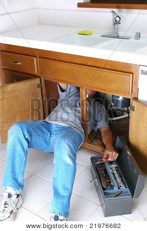 Man with body half under sink cabinet and reaching for wrench in toolbox