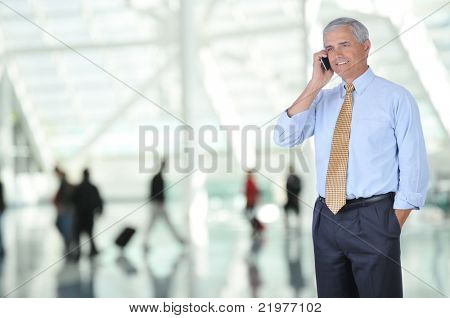 Middle Aged Business Traveler Talking on Cell Phone in Airport Concourse with blurred travelers in background