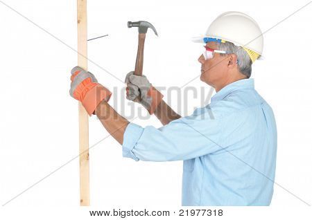 Middle Aged Construction Worker Hammering Nail into Board side view isolated on white