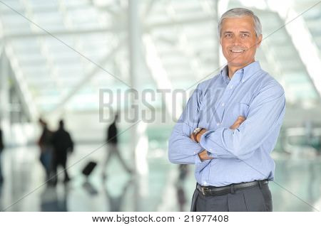 Smiling Middle Aged Businessman with Arms Crossed in Airport Concourse - blurred travellers in background