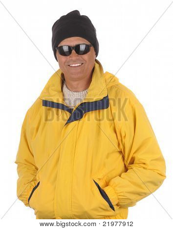 Smiling man in yellow anorak, watch cap and sunglasses isolated over white. Torso only in vertical format.