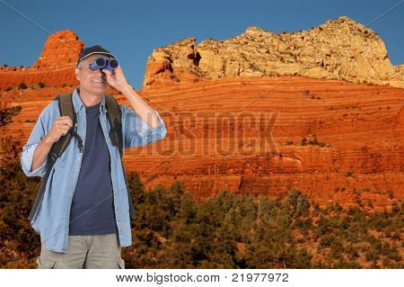 Hiker looking through binoculars at Red Cliffs and rock formations, Sedona, Arizona