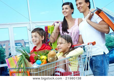 Couple with shopping bags pushing cart with two children