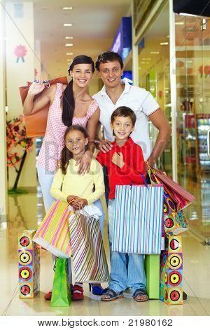 Retrato de uma família feliz de quatro na loja olhando para câmera e sorrir