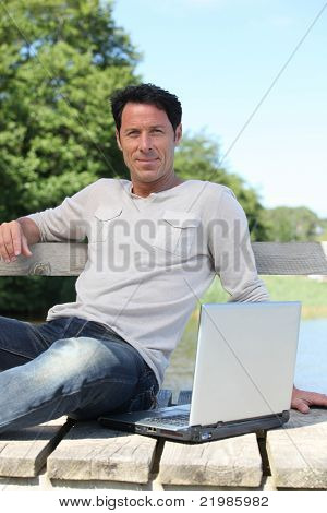 Man sat on park bench with laptop computer