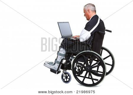 Photo of an injured businessman sitting in a wheelchair working on a laptop computer, isolated against a white background. Laptop screen has a clipping path to add your own message or image.