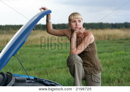 Young Blond Woman With Her Broken Car. The Girl Is Sad
