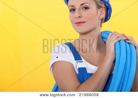 pretty blonde plumber carrying hose