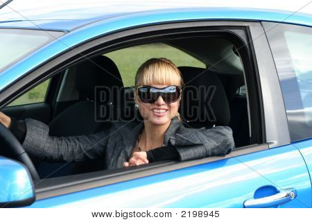Young Blond Woman In A Blue Car In Sun-Glasses