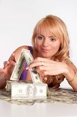 stock photo of pretty girl  - pretty young woman constructing a money house - JPG