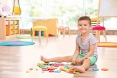 Cute little boy playing with math puzzle at home poster
