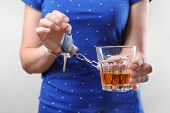 Woman in handcuffs with glass of alcohol and car key against light background. Dont drink and drive poster