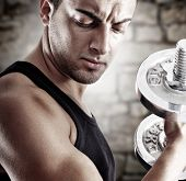 image of lifting weight  - Young man doing weights lifting on stone background - JPG