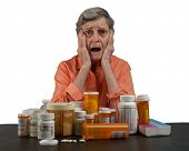 stock photo of elderly woman  - An elderly woman with a tableful of medications looking overwhelmed and confused - JPG