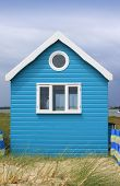 pic of beach-house  - A brightly painted blue wooden constructed beach hut set amongst sand dunes and grasses - JPG