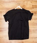 Wrinkled black plain short sleeved cotton T-Shirt on a planket wooden background poster