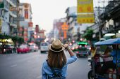 Young Asian Woman Traveler With Blue Backpack And Hipster Hat Looking Night View On Road With Tuk Tu poster