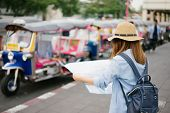 Young Woman Traveler With Sky Blue Backpack And Hat Looking The Map With Tuk Tuk Thailand Background poster