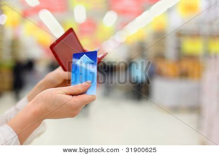 Woman gets credit card from purse in store; shallow depth of field