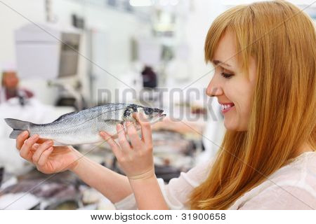 Smiling girl wearing white shirt holds fish in store; shallow depth of field