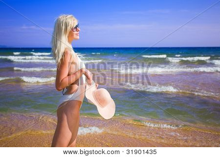 Beautiful girl standing on the seashore. Polarizing filter.