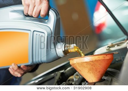 auto mechanic hands replacing and pouring motor oil into automobile engine at maintenance repair service station