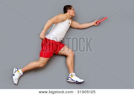Guy with a concentrated look on his face hurrying to pass the relay baton