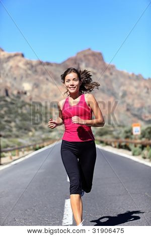Jogging woman. Female runner outdoors running workout in mountain landscape. Beautiful mixed race Caucasian / Chinese Asian female athlete model working out outside.