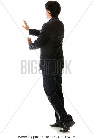 Rear view of a man pushing something - isolated over a white background