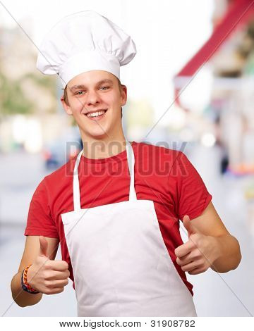portrait of young cook man doing success symbol at street