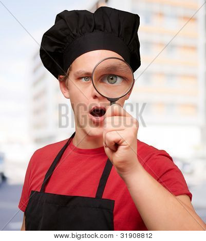 portrait of young cook man looking through a magnifying glass against a building