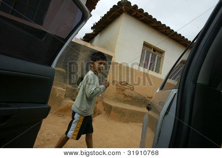 NOVO CRUZEIRO, BRAZIL - JULY 27: An unidentified child walks past a vehicle on July 27, 2005 in Novo Cruzeiro, Brazil. Over 10,000 residents still engage in agriculture, which is mainly subsistence.