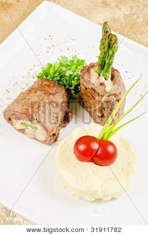 Grilled meat rolls from beef meat with mozzarella, ham, asparagus and mashed potatoes