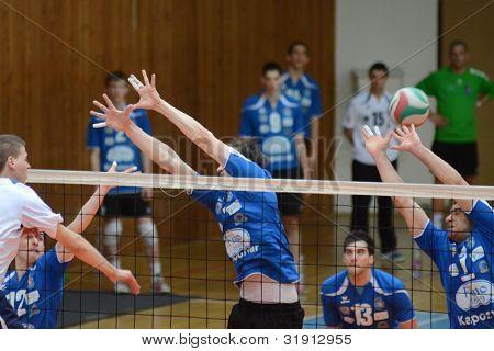 KAPOSVAR, HUNGARY - MARCH 17: Andras Geiger (R) in action at a Hungarian Championship volleyball game Kaposvar (blue) vs. Kazincbarcika (white), March 17, 2012 in Kaposvar, Hungary.