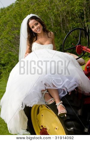Wedding bride sitting on a tractor wearing a white dress