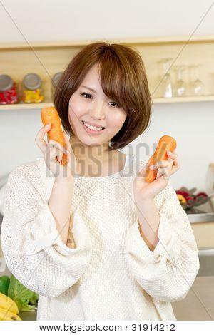 Mujer hermosa en la cocina. Retrato de mujer asiática.